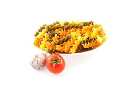 multicolored pasta, one tomato and garlic on a white background photo