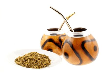 couple of mate cups on and a plate with mate a white background photo