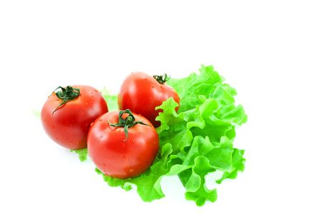 three red tomatos on leaves of lettuce. white background Stock Photo