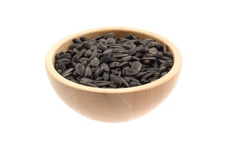 sunflower seeds in a wood bowl. white background