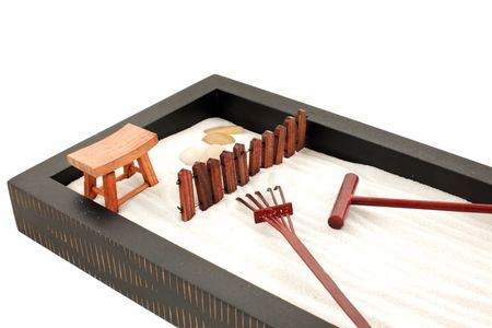 mini zen garden with white sand, stones and wood rakes photo