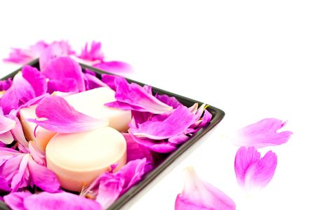 white soap in pink flower petals on a black plate. small GRIP photo