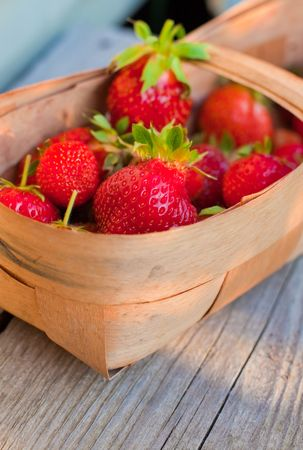 red rich strawberries in twiggen basket on a wood board. small GRIP photo