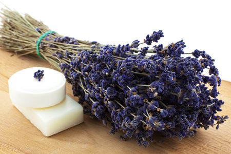 dry lavender bunch with two white soap pieces on a wood board Stock Photo