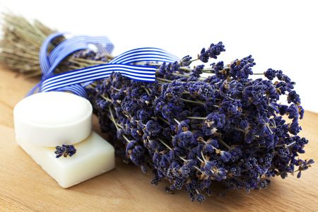 dry lavender bunch with two white soap pieces on a wood board photo