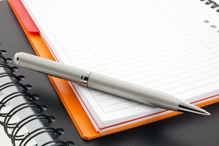 silver pen and two paper notebooks: orange and black photo