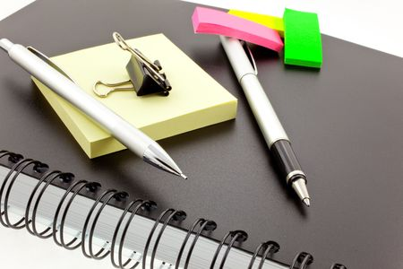 black personal organizer, multicolor post-its, silver pen, pencil and steel clip