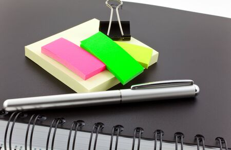 black personal organizer, multicolor post-its and steel clip photo