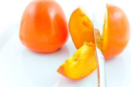 two ripe persimmons and steel knife on a white dish. Macro. Small GRIP photo