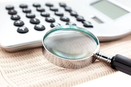 financial newspaper with calculator and magnifier. Closeup. small GRIP Stock Photo