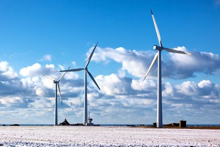 windy energy: modern windmills on blue sea and bright sky background