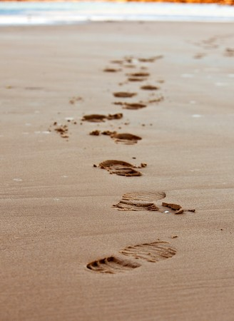 footprints chain on sand of sea coastline. small GRIP Stock Photo