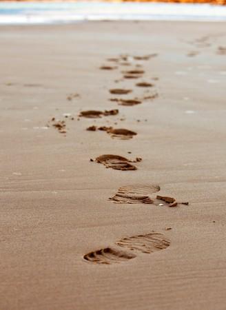 footprints chain on sand of sea coastline. small GRIP Standard-Bild