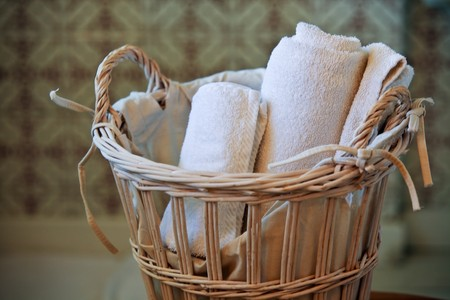 two white rolled towels in wicker basket. small GRIP