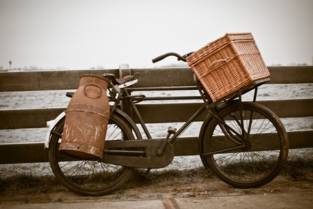 sepia toned: old bicycle with can and basket. retro sepia toned horizontal shot