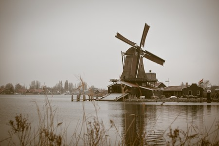sepia toned image of windmill in winter Zaanse Schans. horizontal shot photo