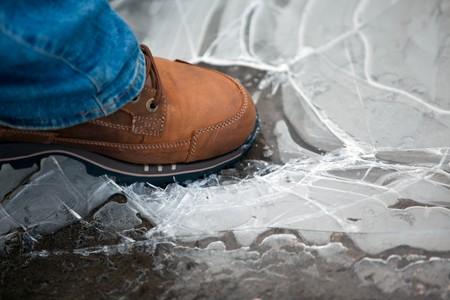 men leg in shoe crushing thin ice. horizontal shot photo
