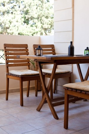 private balcony with wooden chairs and table. vertical shot