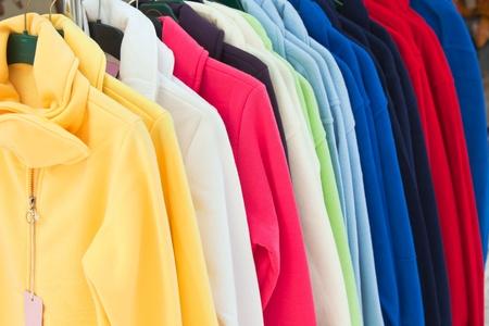 ropa colgada: Coloridas camisetas de deporte de textil en fila en la tienda Foto de archivo
