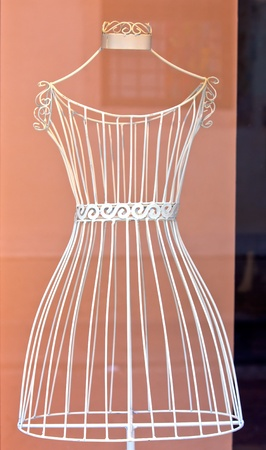 dress form: white metal dress mannequin in store showcase. vertical shot