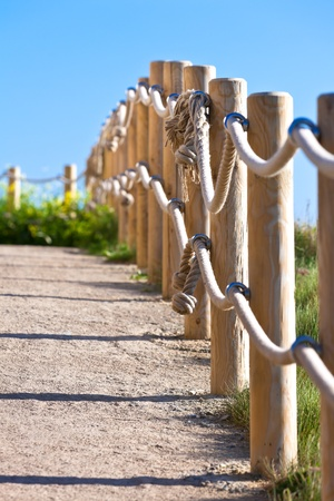 Pathway with wood post and thick rope fence. Taken at Saint-Mathieu, Brittany, France photo