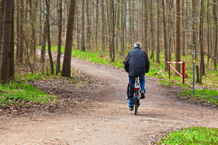 An elderly man riding a bicycle through the woods