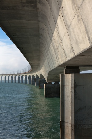 Curved Concrete Bridge over the water. Vertical shot