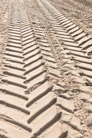 desert footprint: Tractor tire tracks on beach sand. Vertical shot