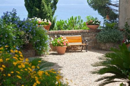 Jardín a la italiana con un banco, el mar como telón de fondo