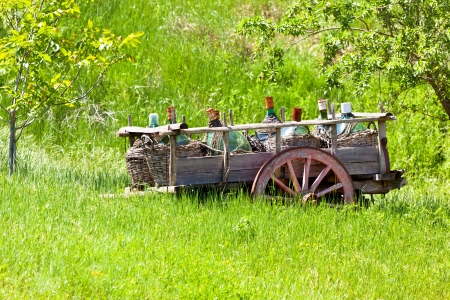 Tuscany landscape: Old Rustic wagon with wine bottles photo