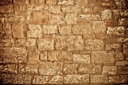 Rough textured limestone brick wall background. Horizontal toned and vignetted image photo