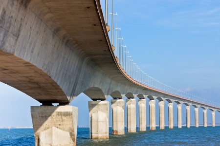 bridges: Curved Concrete Bridge over the water. Horizontal shot Stock Photo