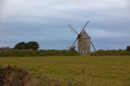 Dull Landscape with Old windmill in Brittany, Western France. Toned image photo