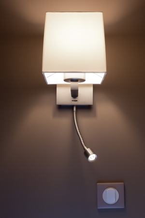 Switched-on lamp in a hotel bedroom. Vertical shot photo
