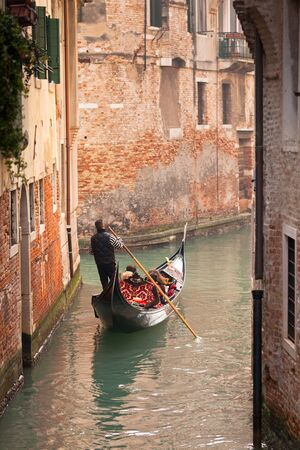 A gondola with tourists going down a small canal lined with urban houses photo