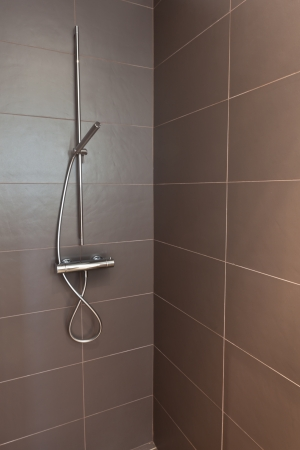 Tiled bathroom shower with stone tiles. Home interiors.