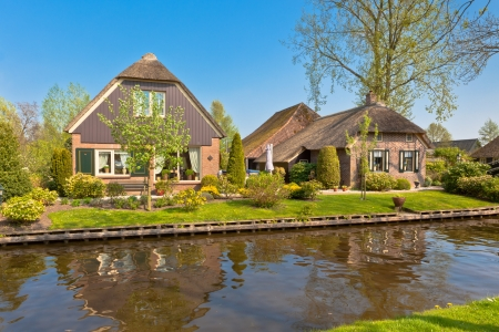 Beautiful traditional houses with a thatched roof on a small island in a Dutch town of Giethoorn Stock Photo