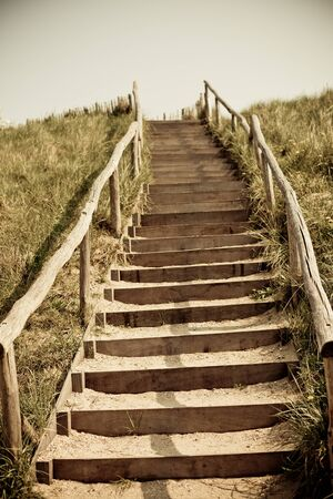 Stairs to the top of a dune. Netherlands. Toned and vignetted image photo