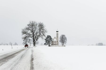 Alpine bavarian Church road and tractor after morning snowfall in mountain village photo