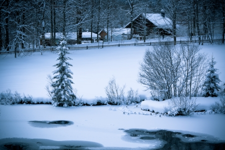 cottage fence: Fairy tale. Snowy Alpine house and frozen river in the woods.ÊToned and vignetted image as postcard
