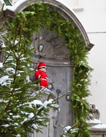 Famous statue of Manneken Pis in Brussels, Belgium wearing Santa Claus clothing for Christmas. photo
