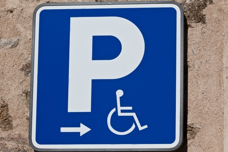 A handicaped parking sign on a house wall  photo