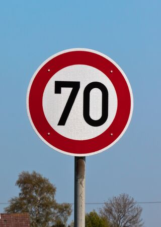 Traffic sign speed limit 70 against blue sky. Vertical shot photo