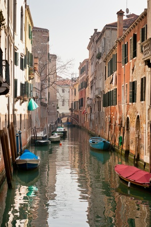 Venetian Canal. Reflections are on the water. photo