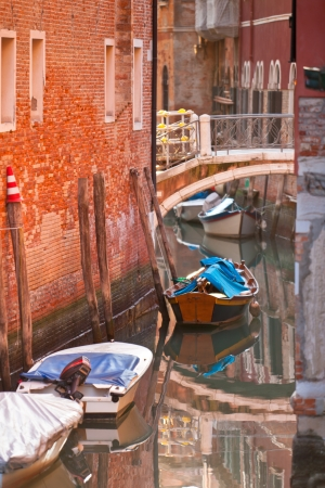 Bridge over a Venetian Canal. Reflections are on the water. photo