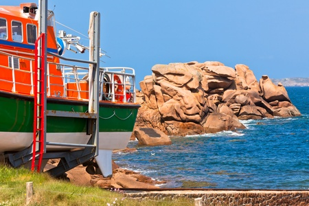 cote de granit rose: Bright boat at Cote de Granit Rose - Pink Granite Coast, Brittany, France Stock Photo