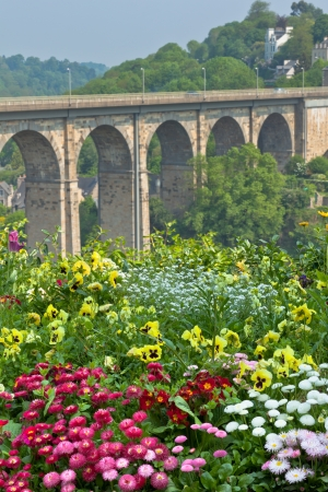 Bright Flowerbed and tall stone bridge as a background photo
