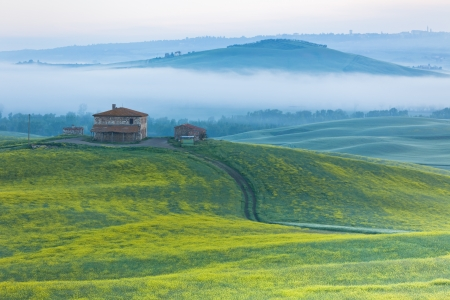 Morning fog view on farmhouse at Valley d?Orcia in Tuscany, Italy photo