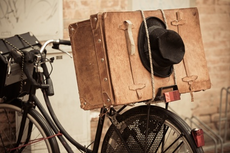 brown leather hat: Shabby black hat and brown suitcase on old bicycle. Retro-styled and sepia toned image Editorial