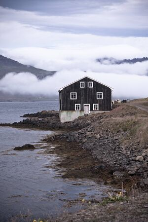 Lonely Black Wooden House at coastline in East Iceland. Vertical toned shot Stock Photo - 16573170